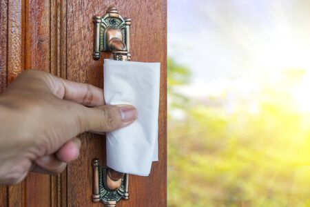 Open the door to protect the virus, protects hand from direct contact with door handle. Paper napkin to protect skin from virus and germs. Banco de Imagens