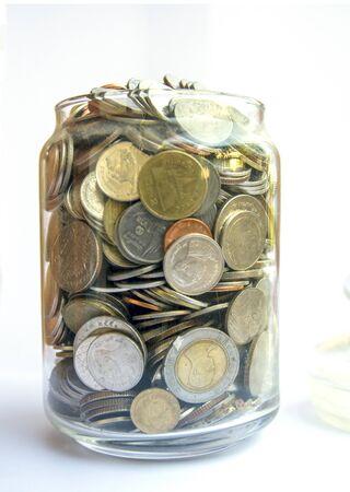 Geldmünzen mit zu Hause, Sparen für das Kaufhauskonzept, Münzen im Glas auf unscharfem Hintergrund. Geld sparendes Finanzkonzept