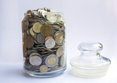 money coins with home, Saving for buy home concept, Coins in glass jar on blur background. money saving financial concept Banco de Imagens