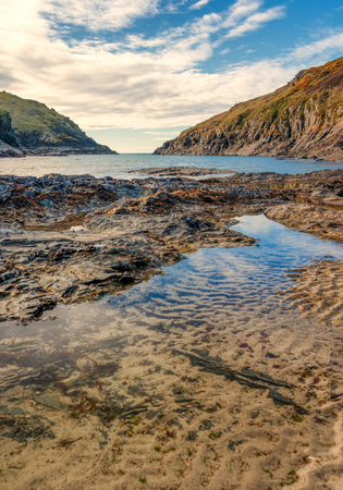 quin: View from the beach at Port Quin, North Cornwall, England, as the tide goes out.