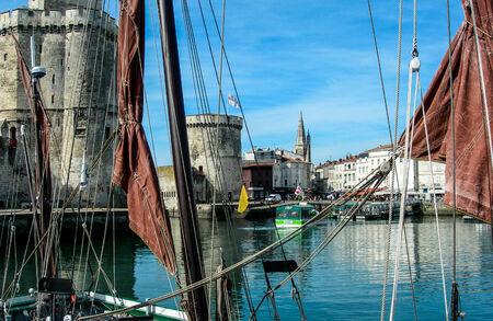 Le Vieux Port at La Rochelle, Charente Maritime, western France, seen through the rigging of an old sailing boat. To the left can be seen la Tour St Nicolas and in the centre la Tour de la Chaine