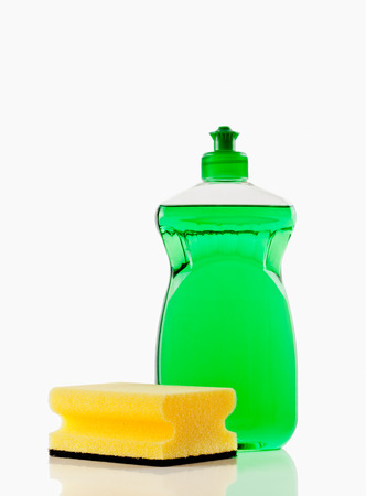Bottle of green bubbling dish liquid with sponge isolated on a white background Standard-Bild