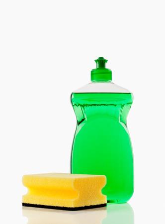 Flasche grüne bubbling Dish-Flüssigkeit mit einem Schwamm auf einem weißen Hintergrund