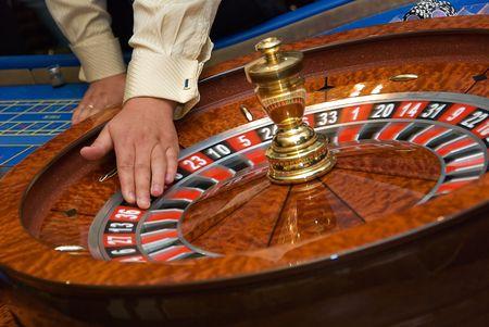 Croupiers hand rotates roulette wheel Stockfoto - 3777586