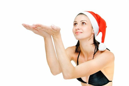 young pretty girl in cap of santa places palms up  photo