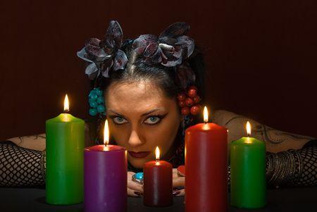 soothsayer: hermosa joven adivino con cinco velas de color rojo oscuro sobre fondo