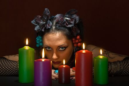 adivino: hermosa joven adivino con cinco velas de color rojo oscuro sobre fondo