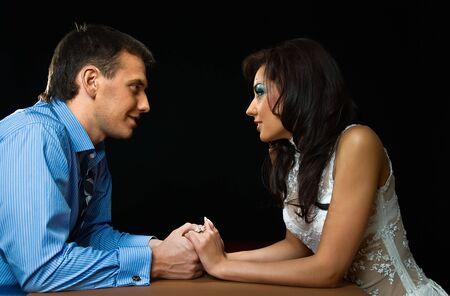 ciascuno: giovane coppia amorosa si siede al tavolo su sfondo nero