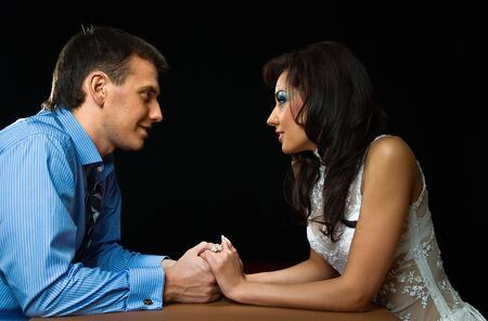 young loving couple sits at the table on black background photo