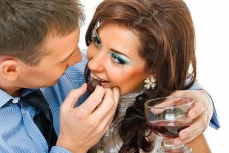 young embracing couple, man treats woman with sweets  photo