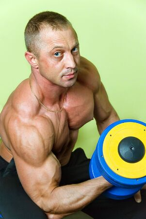 young handsome bodybuilder with dumbbell Stock Photo - 4974281