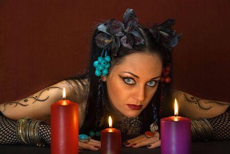 soothsayer: adivino hermosa joven, con tres velas de color rojo oscuro sobre fondo