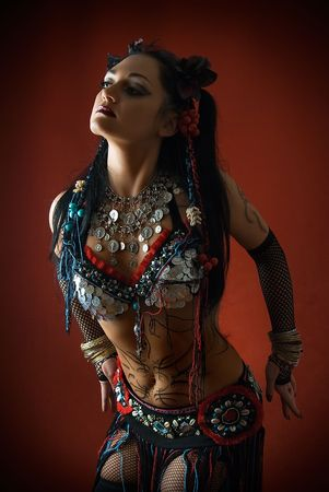 young beautiful tribal dancer woman on red background