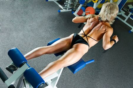 woman bodybuilder does exercise for muscles of back  photo