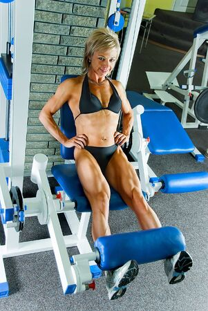 female bodybuilder: woman bodybuilder makes exercise for legs extensor