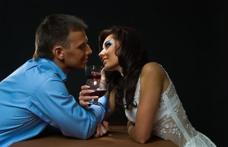 young loving couple sits at the table on black background with glass photo
