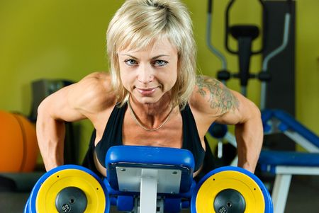 young woman bodybuilder does exercise with dumbbells photo
