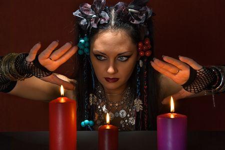 adivino: adivino hermosa joven con tres velas en el fondo de color rojo oscuro Foto de archivo