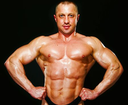 posing man bodybuilder on a black background Stock Photo - 5341061