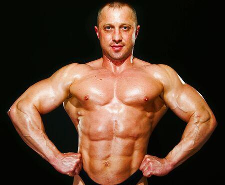 posing man bodybuilder on a black background Stock Photo - 5341061