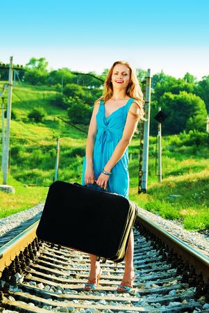 smiling pretty woman on railway with suitcase Stock Photo - 5405031