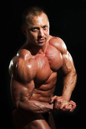 posing man bodybuilder on black background Stock Photo - 5405051