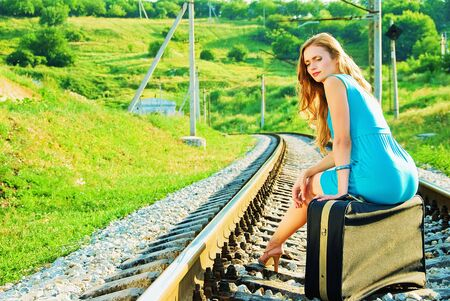 pretty girl sitting on a suitcase on the train tracks Stock Photo - 5433657