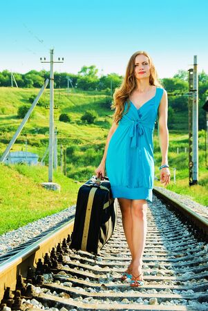 smiling pretty woman on railway with suitcase Stock Photo - 5433638