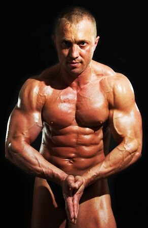 man bodybuilder shows his muscles on black background Stock Photo - 5433563