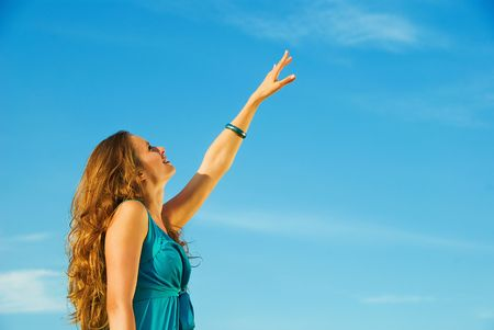 young beautiful woman with hand up to blue sky  photo