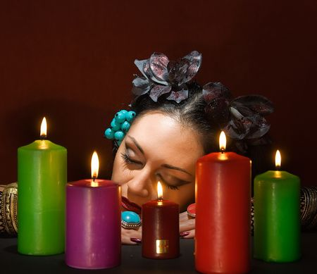 soothsayer: young beautiful soothsayer sleeps about  five candles  Stock Photo