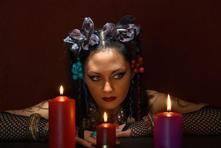adivino: adivino hermosa joven con tres velas sobre fondo rojo oscuro