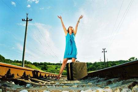 smiling pretty woman on railway with suitcase, she holds hands up to the sky  Stock Photo - 5527092