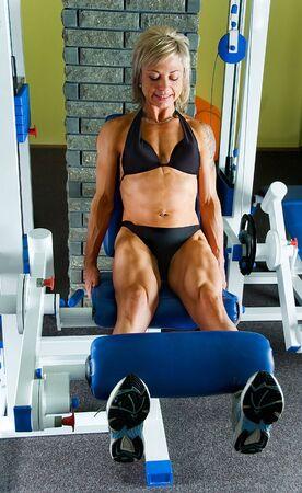 woman bodybuilder makes exercise for legs extensor photo