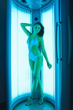 posing beautiful girl in swimsuit  at vertical solarium