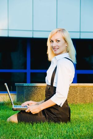 young busines woman with laptop on green grass photo