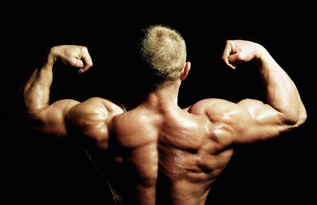 posing bodybuilder from back on black background photo