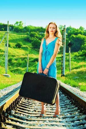 baggage train: sad pretty woman on railway with suitcase
