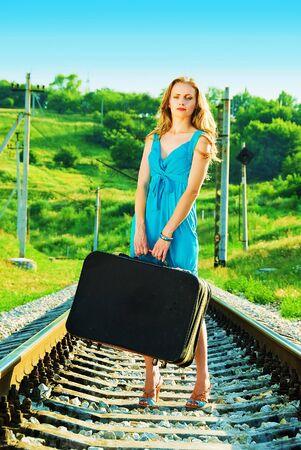 sad pretty woman on railway with suitcase Stock Photo - 6412503