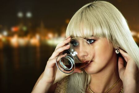 beauty blond girl with wine on night city background photo