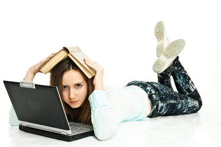 lying young pretty girl about laptop with book on head on white background  photo