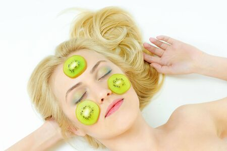 beauty girl with kiwi on cheeks over white background photo