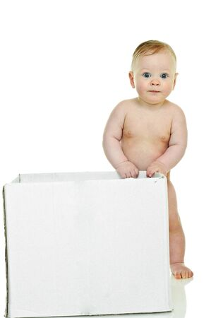 eight month baby holds on to the white box Stock Photo - 6928735