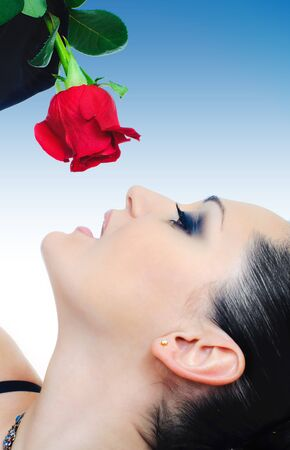 portrait of brunette with red rose on blue background Stock Photo - 7470956