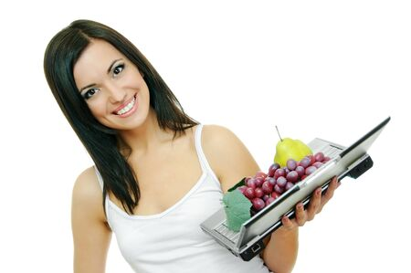 beauty brunette with laptop and fruits on white photo