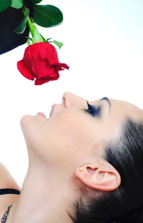 portrait of brunette with red rose on white background photo
