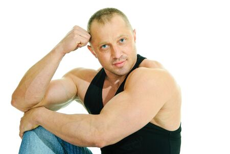 man bodybuilder in jeans and black sleeveless sits on white background photo