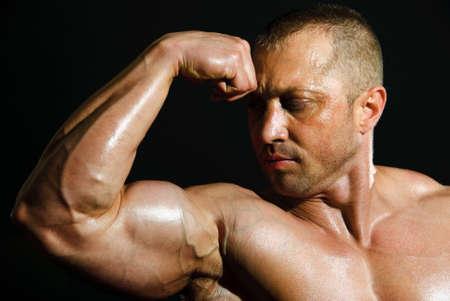 posing man bodybuilder on a black background photo