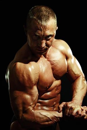 posing man bodybuilder on black background photo
