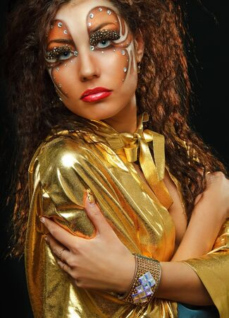 vouge: young beauty girl with art make up in gold mant on black